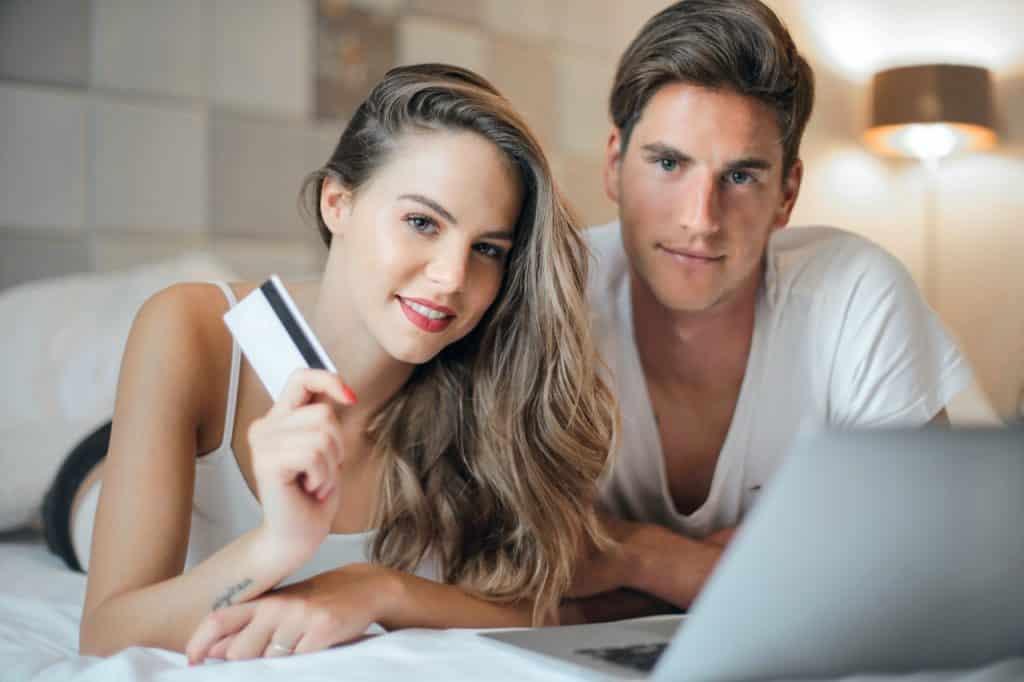 Couple sur un lit avec carte bancaire en main