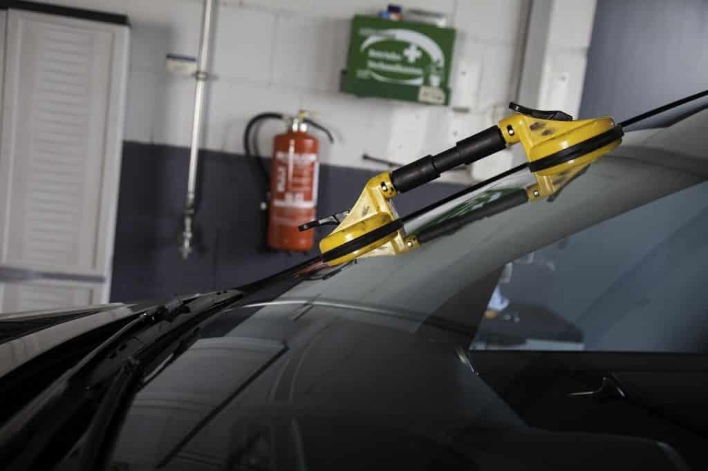 Pare-brise d'une voiture en réparation, avec poignet ventouse