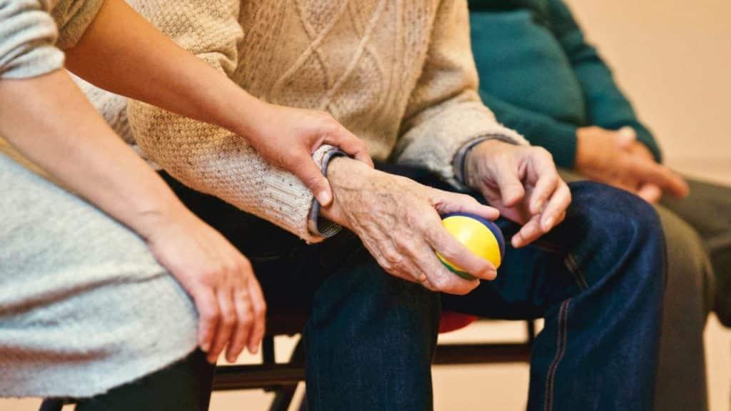 Personne âgée travaillant ses mouvements la pression de ses main avec une balle et de l'aide