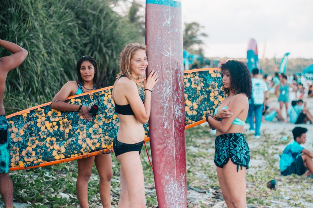 Filles avec des planches de surf sur la plage