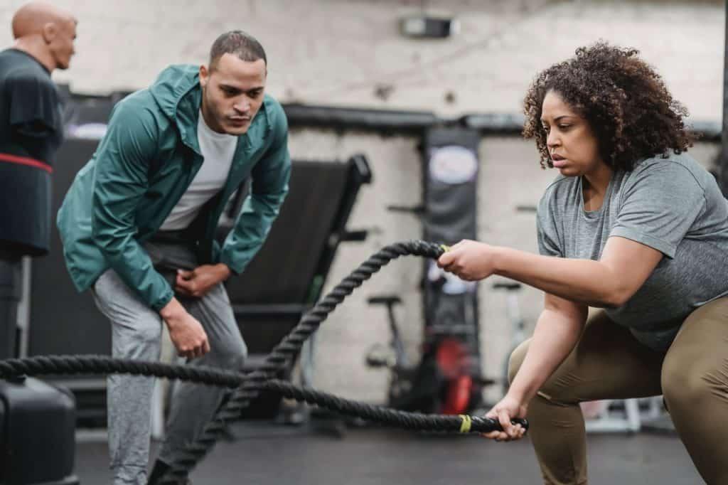 Coach sportif, homme coachant une femme