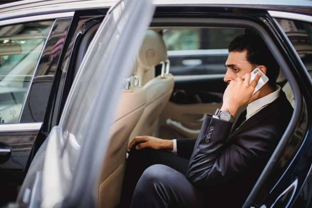 Homme au téléphone dans une voiture avec chauffeur
