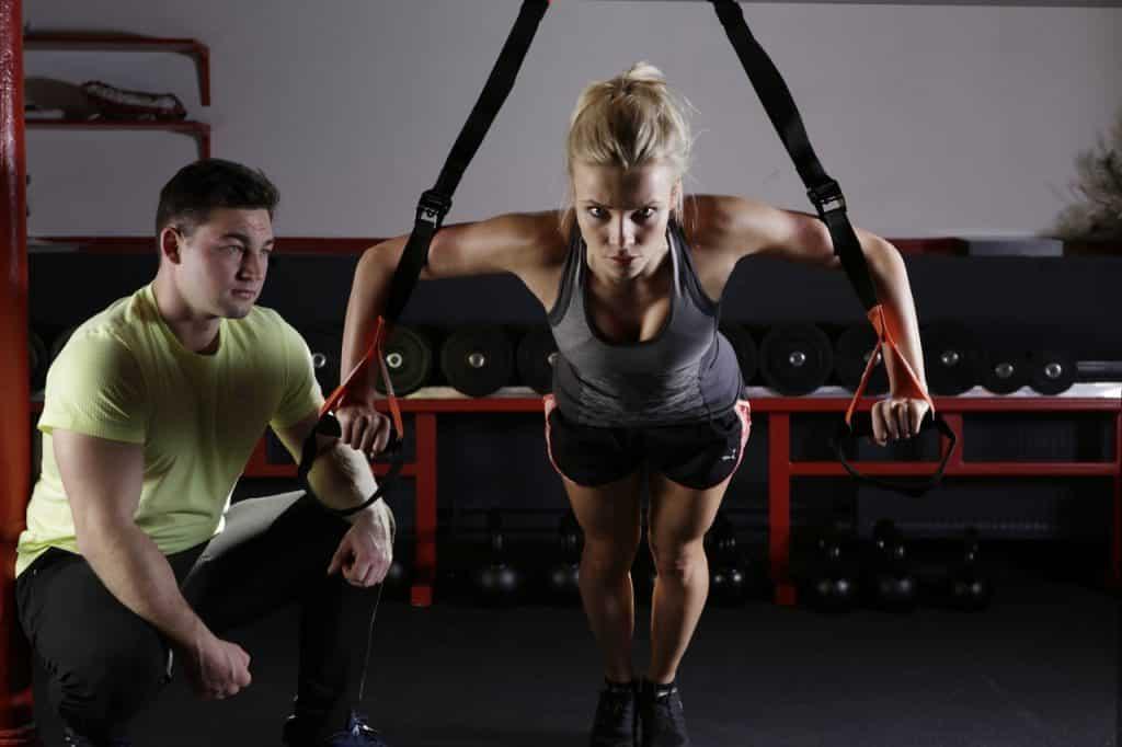 Femme faisant musculation avec l'aide d'un coach sportif